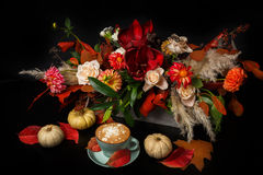 Cappuccino coffee and flowers composition on black background Royalty Free Stock Photos