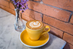 Cappuccino coffee of a heart shaped in a yellow cup near purple. Flowers in a vase and brick Background stock photo