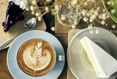 Cappuccino coffee with latte art and cake slice desserts. On table royalty free stock images
