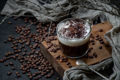 Cappuccino coffee with milk foam and chocolate on a wooden board with additional accessories. Horizontally oriented frame.  royalty free stock image