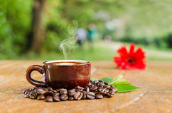 Cappuccino Coffee in a mug. Coffee in a mug & beans with flower and leaves Stock Image