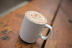 Cappuccino coffee mug on table Royalty Free Stock Images