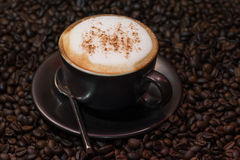 Cappuccino coffee over roasted coffee beans as background Stock Photo