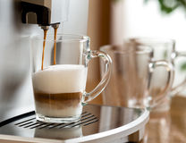Cappuccino coffee preparing in glass cup with machine Stock Images