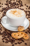 Cappuccino coffee and spilled coffee beans Royalty Free Stock Photography
