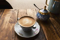 Cappuccino coffee, in vintage porcelain cup, on the wooden table Royalty Free Stock Image