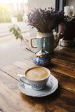Cappuccino coffee, in vintage porcelain cup, on the wooden table Stock Photography