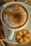 Cappuccino coffee in a white cup. with cinnamone and biscuits Stock Image