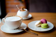 Cappuccino coffee in white cup with colorful macaroons served on wooden table royalty free stock photos
