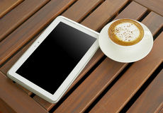 Cappuccino coffee white cup with 10 inch touch screen tablet bank display on wooden table Stock Image