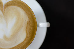 Cappuccino coffee in a white cup and saucer on a black wooden ba Royalty Free Stock Photos