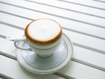 Cappuccino coffee in white cup on wooden Royalty Free Stock Photos