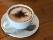 Cappuccino coffee in white cup on wooden table. Cappuccino coffee in white cup on wooden table Royalty Free Stock Images