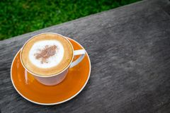 Cappuccino coffee in white cup on wooden table in garden.  Stock Photos