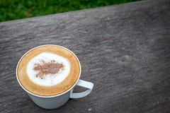 Cappuccino coffee in white cup on wooden table in garden.  Royalty Free Stock Photo