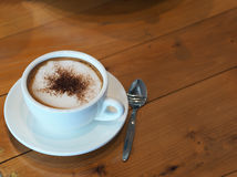 Cappuccino coffee in white cup on wooden table, Top view. Cappuccino coffee in white cup on wooden table, Top view Royalty Free Stock Image