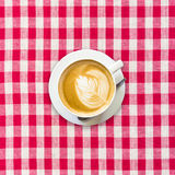 Cappuccino coffee on white and red checkered background Stock Images