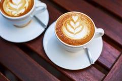 Cappuccino com arte do latte na tabela de madeira Imagens de Stock