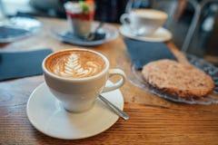Cappuccino com espuma bonita e colher no copo Fotografia de Stock