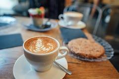 Cappuccino com espuma bonita e colher no copo Imagem de Stock