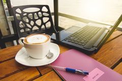 Cappuccino com um caderno em uma cafetaria Imagem de Stock Royalty Free