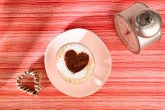 Cappuccino con el viejos reloj de alarma y corazón Imagenes de archivo
