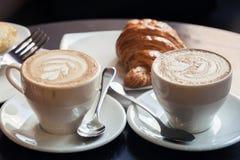 Cappuccino con il croissant Due tazze di caffè Fotografie Stock
