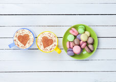 Cappuccino con il simbolo e il macaron di forma del cuore Immagini Stock Libere da Diritti