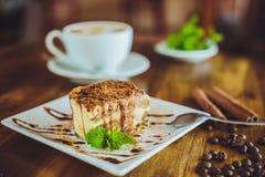Cappuccino con il tiramisù sulla tavola di legno Immagini Stock
