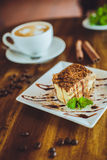 Cappuccino con il tiramisù sulla tavola di legno Fotografie Stock