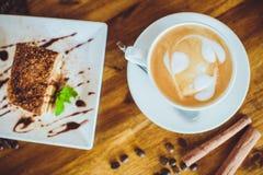 Cappuccino con il tiramisù sulla tavola di legno Fotografia Stock