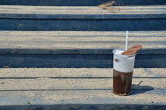 Cappuccino with a cookie on beach stairs Stock Photography