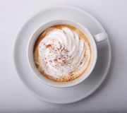 Cappuccino with cream. In white cup and a plate Royalty Free Stock Images