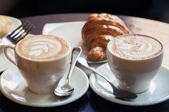 Cappuccino with croissant. Two cups of coffee Stock Photos