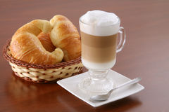Cappuccino and croissants. Cappuccino and Argentine croissants (medialunas) on wood table Stock Image