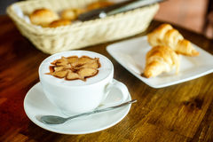 Cappuccino and croissants on a brown background Stock Photo