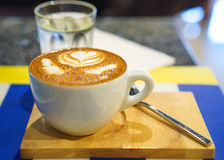 Cappuccino cup on the brown wooden table Royalty Free Stock Images