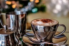 Cappuccino Cup with a Christmas background. A hot cup of Cappuccino in a silver cup with pots of milk and sugar in selective focus with Christmas fairy lights Royalty Free Stock Image