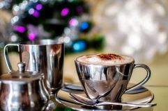 Cappuccino Cup on a colorful Christmas background. A hot cup of Cappuccino in a silver cup with pots of milk and sugar in selective focus with Christmas fairy Royalty Free Stock Image