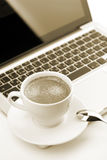Cappuccino cup on laptop Stock Photo