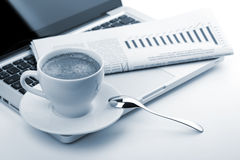 Cappuccino cup with laptop and newspaper Royalty Free Stock Image