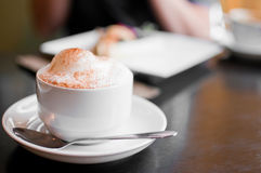 A cappuccino cup with milk foam. And cinnamon Stock Image