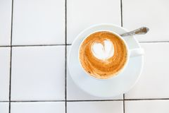 Cappuccino cup on tiled white table background. Foam is decorated with cinnamon heart. Copy space. Top view. stock photo