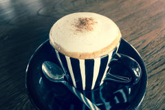 Cappuccino in a cup on a wooden table - vintage effect Stock Photo