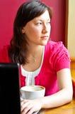 Cappuccino da mulher nova e portátil bebendo da utilização Foto de Stock Royalty Free