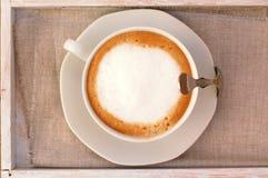Cappuccino dans la tasse sur le tissu Photo stock