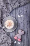 Cappuccino de café avec le lapin de cannelle et de pain d'épice avec le coeur sur un fond en bois gris Jour heureux du `s de Vale Photo stock