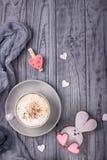 Cappuccino de café avec le lapin de cannelle et de pain d'épice avec le coeur sur un fond en bois gris Jour heureux du `s de Vale Images stock