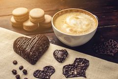 Cappuccino de café avec de prochains macarons de belle mousse et coeur de chocolat Photos libres de droits