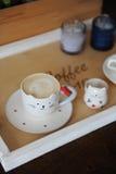 Cappuccino de café dans la tasse mignonne sous forme de chat Sur un plateau en bois Bougies sur le fond Images stock